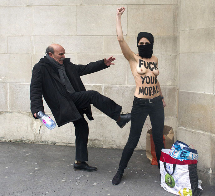 Angry old man kicking bare-chested Femen activist.